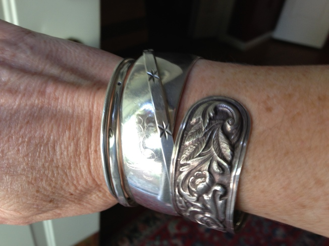 "The shiny silver cuff is hers; we share the same initials and so I asked for it. The bangle with the heraldic stars on it has long fascinated me, ever since I was a child and the far right is a gift she gave me on my 10-year anniversary, a cuff fashioned after our shared silver pattern, ""Repousse"" which I believe has been retired. These are all unique pieces and the sound of them jangling into one another is a sound I grew up with; it is her sound and whenever I hear it, even when she was alive, I thought of her. The first two are also gifts, the front one from her when I had my first son, and the second one my father gave me when I turned 18. Wearing these pieces helps me stay connected to her..."